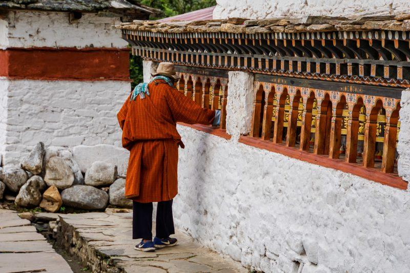 Man loopt langs gebedsmolens in Kyichu Lhakhang in Paro, Bhutan