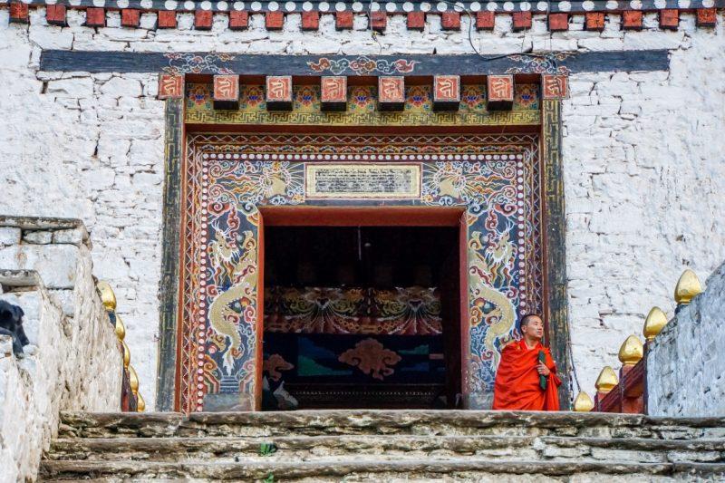 Monnik bij de ingang van Paro Dzong, Bhutan