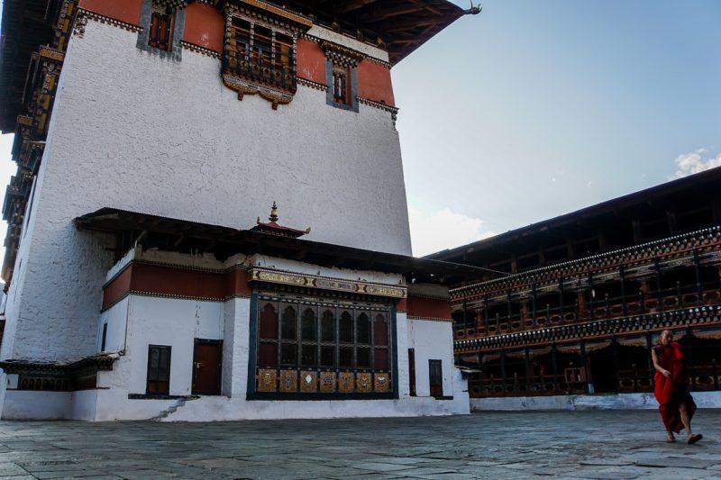 Monnik loopt over het binnenplein in Paro Dzong, Bhutan