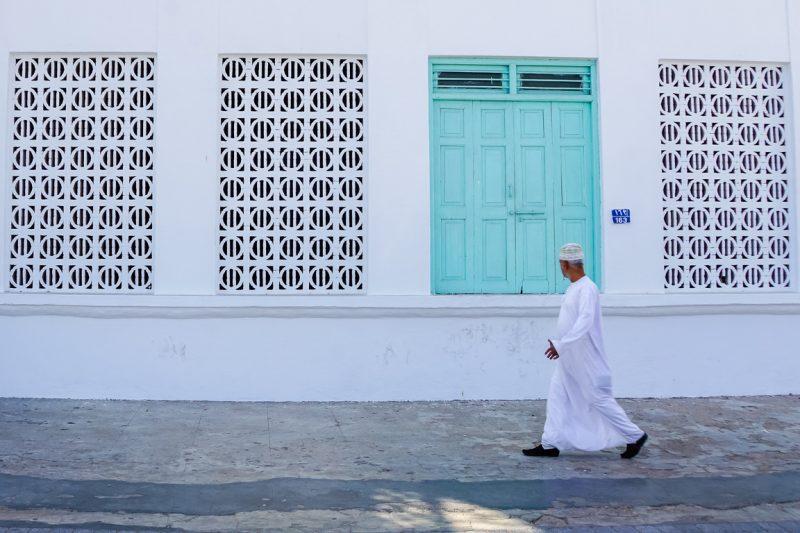Een man wandelt over Mutrah corniche in Muscat, Oman