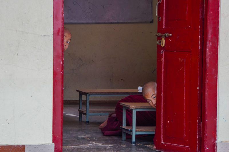 Kleine monniken achter een deur in Gangtok in Sikkim, India